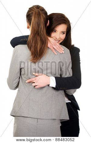 Beautiful businesswoman embrace woman with fingers crossed.
