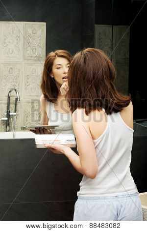 Woman applying lipstick in bathroom.