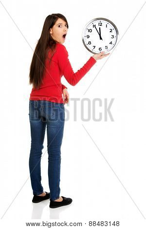 Young shocked student woman with the clock.