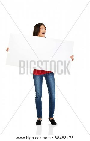 Happy student woman holding empty banner.