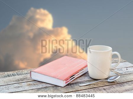 Notebook And Coffee Cup On Wooden Table Over Blurred Background