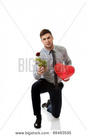 Young happy man kneeling with red rose and heart balloon.