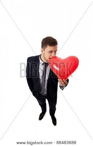 Handsome businessman with heart shaped balloon.