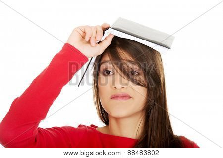 Young student woman with notebook on head.