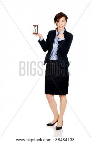 Beautiful shocked businesswoman holding hourglass.