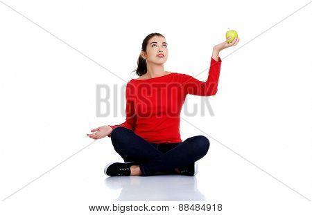 Woman sitting cross-legged holding an apple.