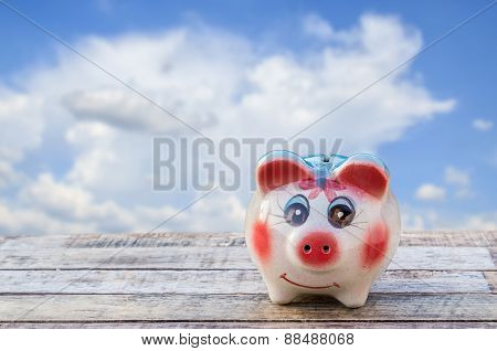 Piggy Bank On Wooden Table Over Blurred Blue Sky Background