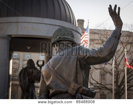 TRENTON, NJ - APRIL 4, 2015: The bronze Lone Soldier sculpture stands behind Lady Victory at the New Jersey World War II Memorial in Trenton, NJ across from the State House capitol building.
