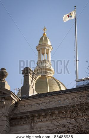 TRENTON, NJ - APR 4 2015: The flag of New Jersey waves in front of the gold dome rotunda of the New Jersey State House capitol building located in Trenton, NJ on State St.