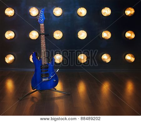 Music Concept. Electric Guitar Standing On The Wooden Floor Near The Wall