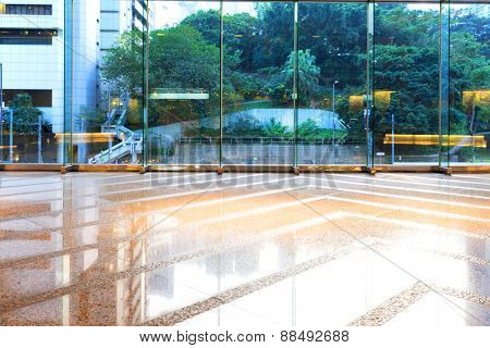 Empty floor and transparent glass wall in modern building corridor