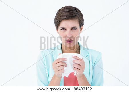 Sick woman holding a tissue and looking at camera on white backround