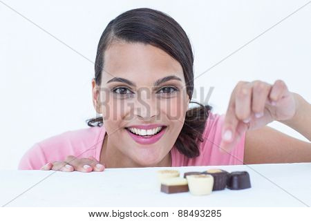 Pretty brunette peeking at chocolate looking at camera on white background