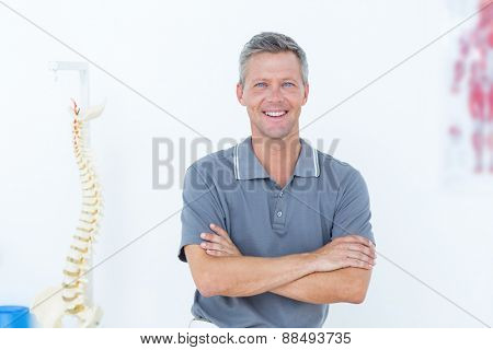 Smiling doctor standing arms crossed in medical office