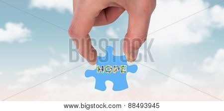 Hand holding jigsaw piece against blue sky
