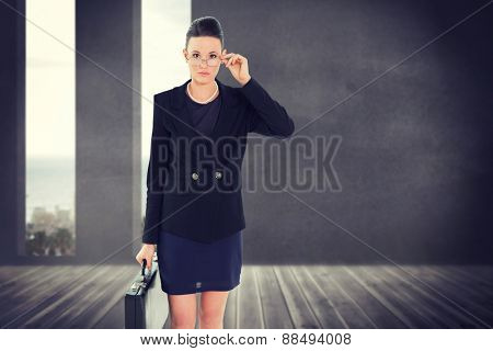 Elegant businesswoman in suit carrying briefcase against grey room with windows showing the ocean