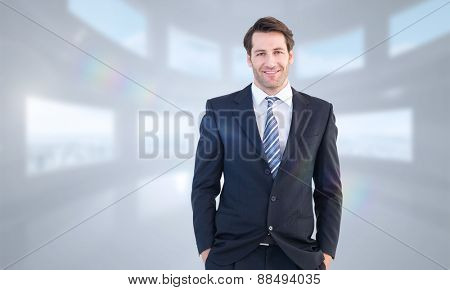 Smiling businessman standing with hands in pockets against bright white room with windows