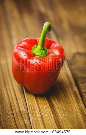 Red pepper with water drops on wooden background