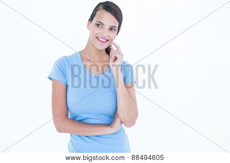 Thoughtful woman smiling with finger on cheek on white background