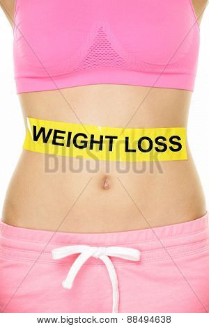 Weight loss concept - Woman waist and belly lower body crop with text on yellow label showing the words written for losing fat with dieting or exercising. Female body with casual pink sports clothing.