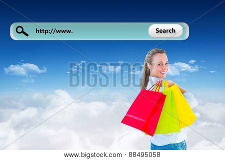 Smiling blonde holding shopping bags against bright blue sky over clouds