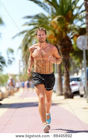 Fit man runner training cardio running in city. Handsome young male adult in his 20s jogging shirtless during warm summer day on a sidewalk in tropical urban background. Sexy athlete with tanned skin.