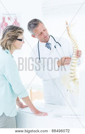 Doctor having conversation with his patient and showing spine model in medical office
