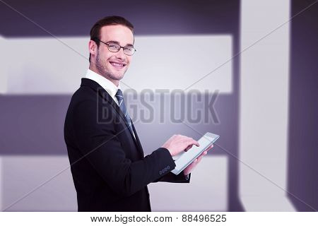Happy businessman using his tablet pc against abstract room