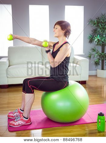 Fit woman lifting dumbbell sitting on ball at home in the living-room