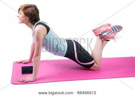 Pretty brunette doing press up on fitness mat on white background