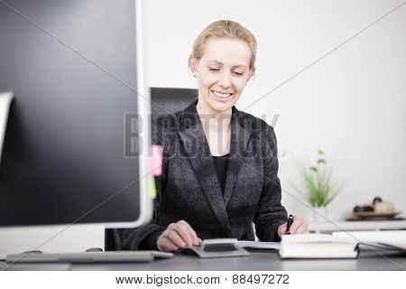 Happy Businesswoman Calculating At Her Worktable