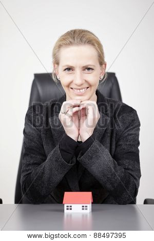 Businesswoman Leaning On Table With Toy House