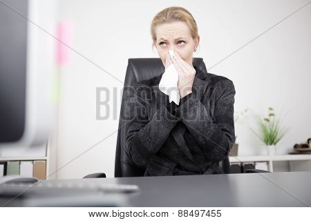 Businesswoman Blowing Her Nose At Her Office