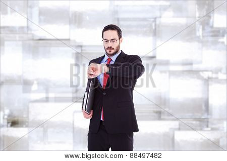 Frowning young businessman checking time against abstract background