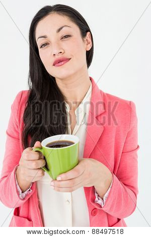 Smiling brunette holding coffee on white background