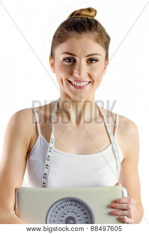Slim woman holding scales and measuring tape on white background