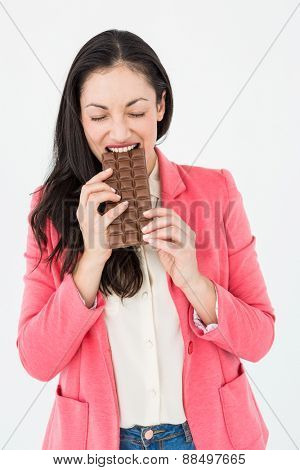 Smiling brunette biting bar of chocolate on white background