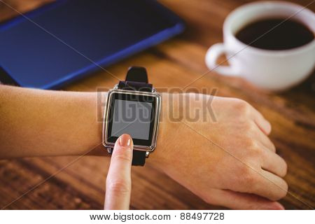 Woman using her smartwatch on wooden table