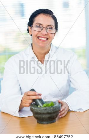Scientist mixing herbs with pestle and mortar in laboratory