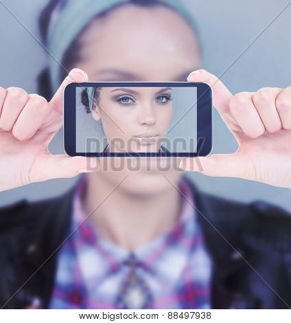 Hands holding smartphone against beautiful woman with hairband posing and looking at camera