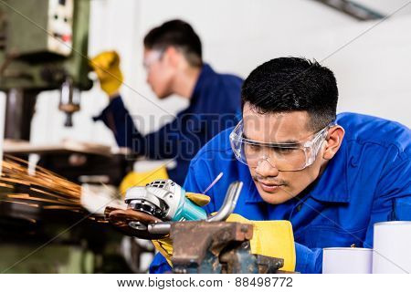 Two Asian industrial workers in metal factory with electrical grinding tool and power drill machine