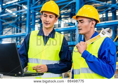 Worker in Asian production plant with laptop discussing