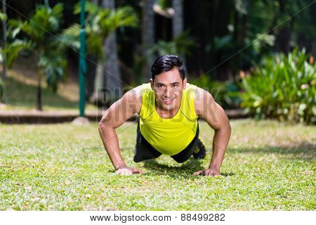 Strong Asian man doing sport push-up in park looking at camera