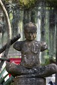 image of figurines  - Ceramic figurine in a tropical garden - JPG