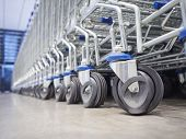 stock photo of trolley  - Trolley supermarket wheel in row Close up - JPG