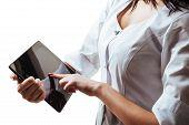 stock photo of scrubs  - Young woman doctor in scrubs using a touchscreen computer - JPG