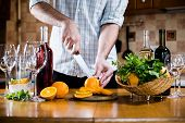 pic of sangria  - Man cuts oranges for making sangria for home party - JPG