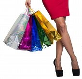 pic of crossed legs  - Womans crossed legs and hand holding colorful shopping bags - JPG