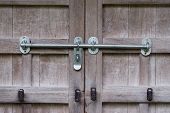 foto of lock  - An old wooden door with rusty old locks and newer silver locks - JPG