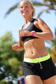 stock photo of cardio exercise  - Happy female marathon runner running listening music with earphones on smartphone and wearing a tech smartwatch activity tracker or a heart rate monitor sportswatch - JPG